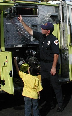 Firefighter Shows Child Firefighting Equipment