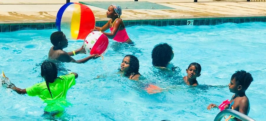 kids playing with ball in pool at pool party