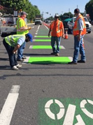 Public Works Personnel Apply Paint Signs on the Road