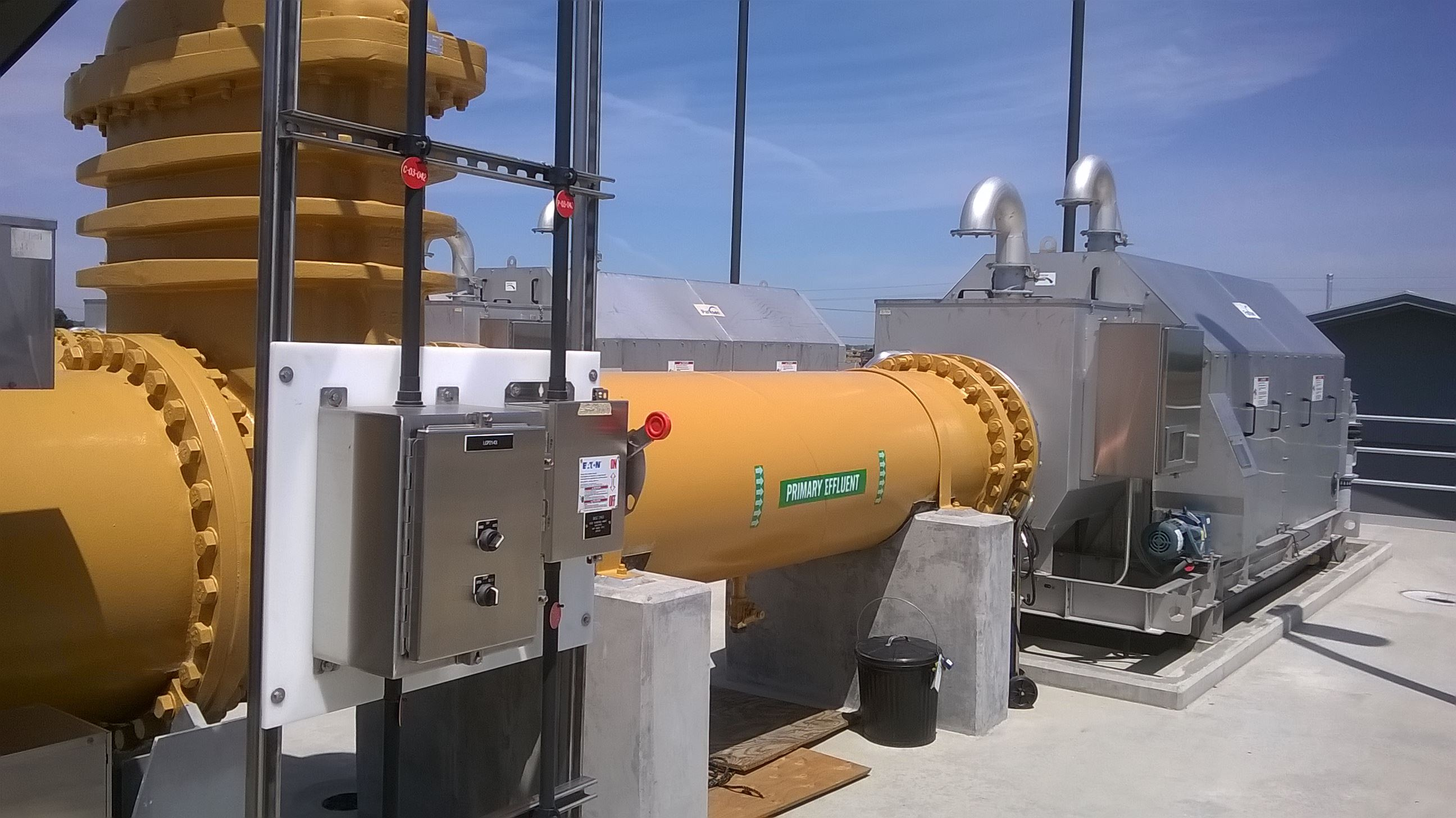 a large pipe feeds wastewater into an enclosed quarter inch screen filter to remove any remaining solids